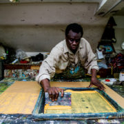 Wilson, a Sudanese refugee artist, works on a silkscreen in the basement of the All Saints Cathedral in Cairo in 2016.